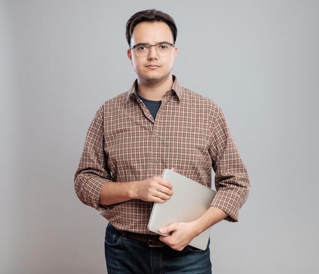 Zufälliger junger mann im hemd mit laptop