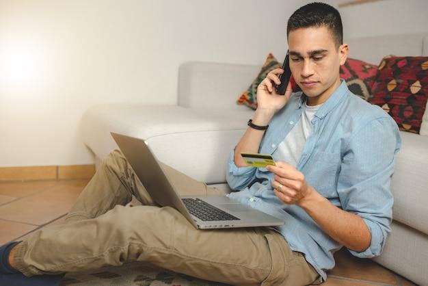 Zufälliger junger mann zu hause auf computer-laptop, der kreditkarte und smartphone hält.