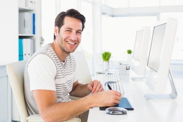 Zufälliger mann, der am schreibtisch mit computer und analog-digital wandler arbeitet