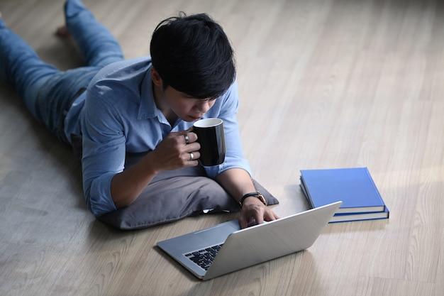 Zufälliger mann, der auf holzboden liegt, kaffee trinkt und an laptop-computer arbeitet.