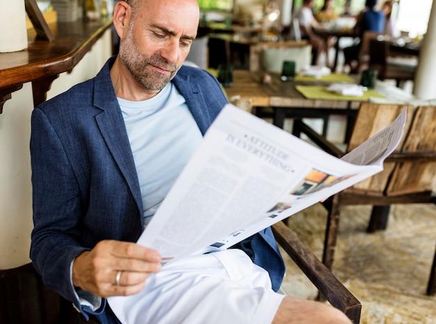 Zufälliger mann, der eine zeitung an einem restaurant liest