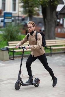 Zufälliger mann, der einen elektroroller reitet