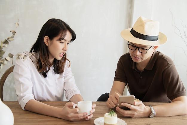 Zufälliger mann und frau, die glücklich spricht, während kaffee trinken und handy schauen
