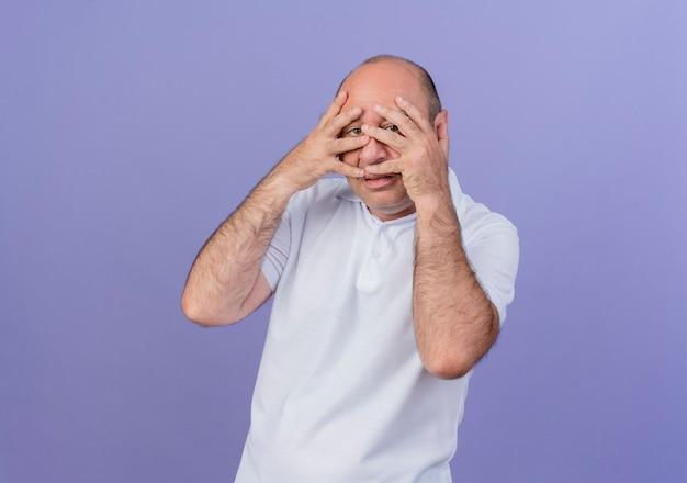 Zufälliger reifer geschäftsmann, der hände auf gesicht setzt und kamera durch finger lokalisiert auf lila hintergrund mit kopienraum betrachtet