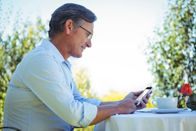 Zufälliger reifer geschäftsmann unter verwendung des smartphone