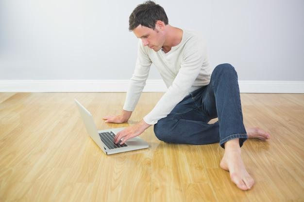 Zufälliger ruhiger mann, der auf boden unter verwendung des laptops sitzt