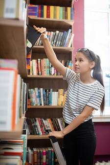 Zufälliger weiblicher teenager, der durch bücherregal in der hochschulbibliothek steht und buch nimmt, während er sich auf die lektion vorbereitet
