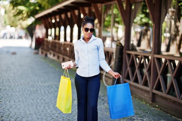 Zufälliges afroamerikanermädchen mit dem farbigen einkaufstaschegehen im freien. stilvolles einkaufen der schwarzen frau.