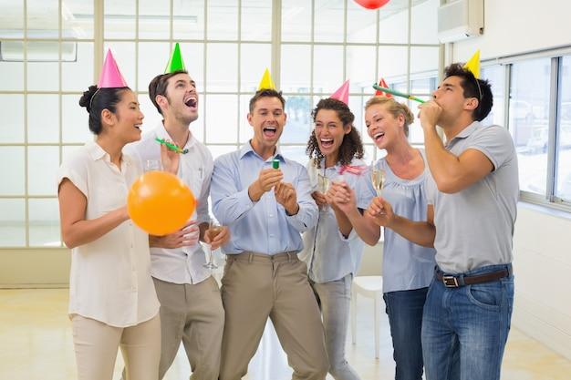Zufälliges geschäftsteam, das mit champagner und partei poppers feiert