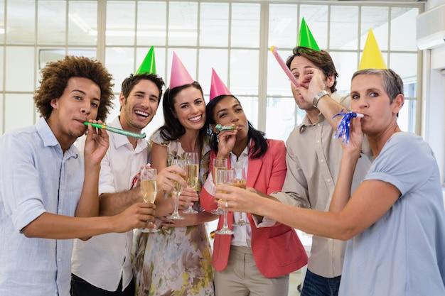 Zufälliges geschäftsteam, das mit champagner- und parteihörnern feiert