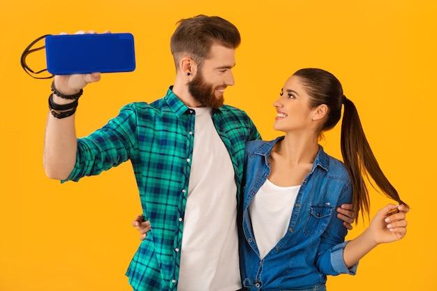Zufälliges junges paar, das drahtlosen lautsprecher glücklich hält, der musik hört, die bunte art glückliche stimmung tanzt, lokalisiert auf gelber wand
