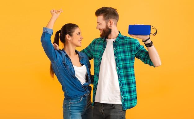 Zufälliges junges paar, das drahtlosen lautsprecher hält, der die glückliche stimmung des tanzes der bunten art der musik lokalisiert auf gelbem hintergrund hört