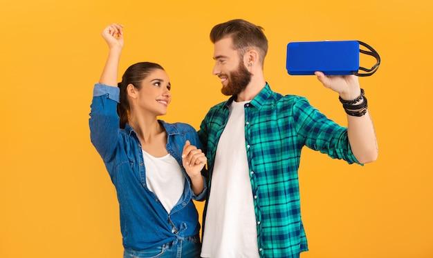 Zufälliges junges paar, das drahtlosen lautsprecher hält, der musik hört, die auf orange tanzt