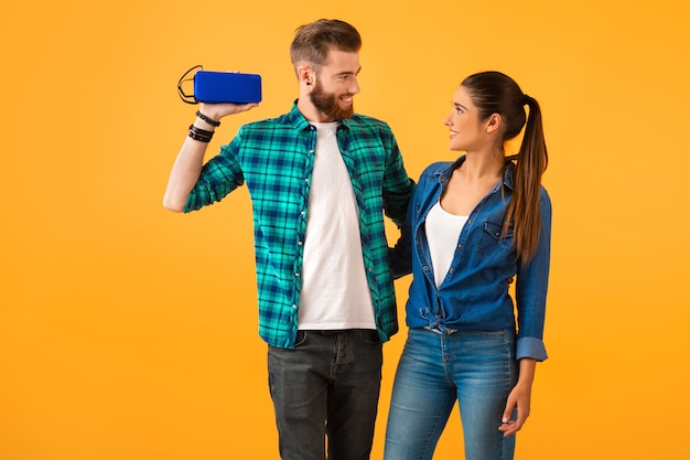 Zufälliges junges paar, das drahtlosen lautsprecher hält und musik hört