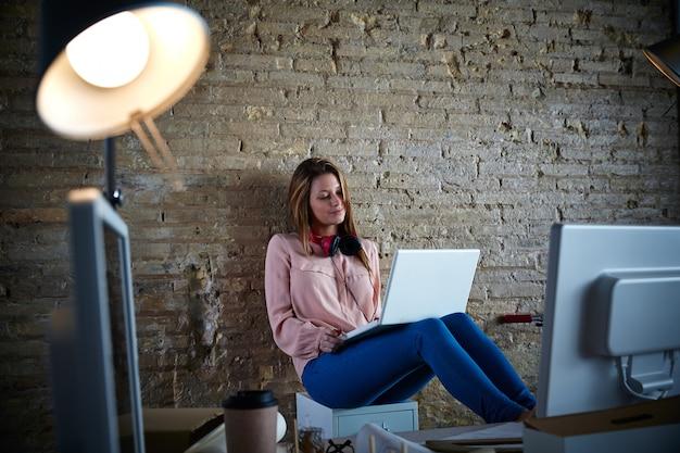 Zufälliges sitzen der geschäftsfrau im büro mit laptop