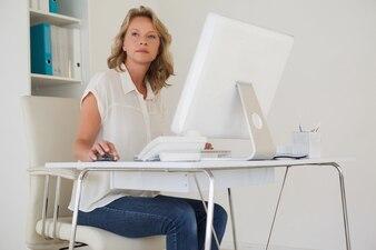 Zufällige Geschäftsfrau, die an ihrem Schreibtisch denkt