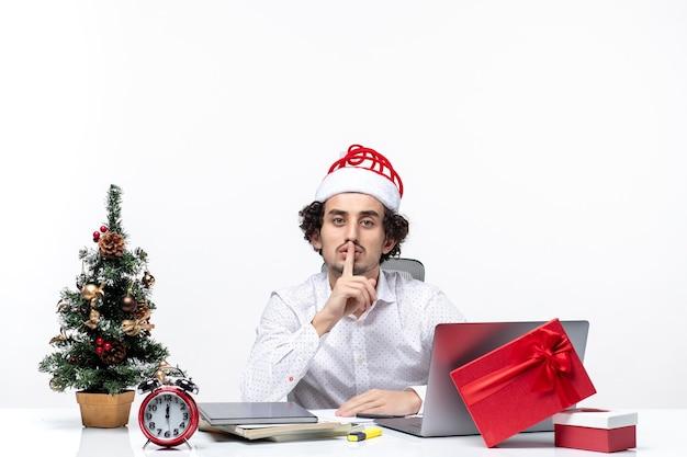 Zufrieden beschäftigter stolzer junger geschäftsmann mit lustigem weihnachtsmannhut, der weihnachten feiert und stille geste im büro auf weißem hintergrund macht