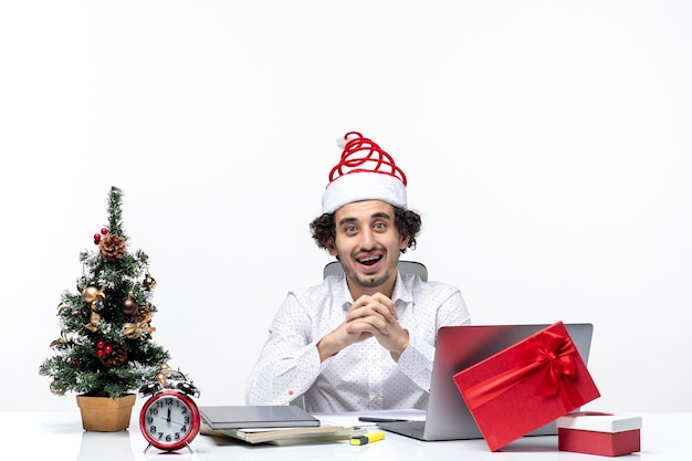 Zufrieden beschäftigter stolzer junger geschäftsmann mit lustigem weihnachtsmannhut, der weihnachten im büro auf weißem hintergrund feiert