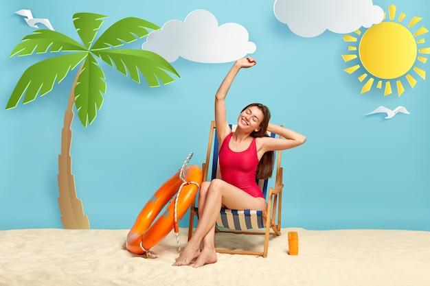 Zufrieden entspannt entspannt schöne urlauberin streckt sich im liegestuhl, trägt roten bikini