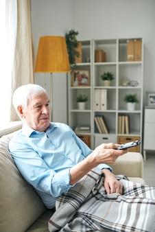 Zufrieden entspannter älterer mann mit decke auf beinen, die auf sofa sitzen und fernbedienung verwenden, während sie allein zu hause fernsehen