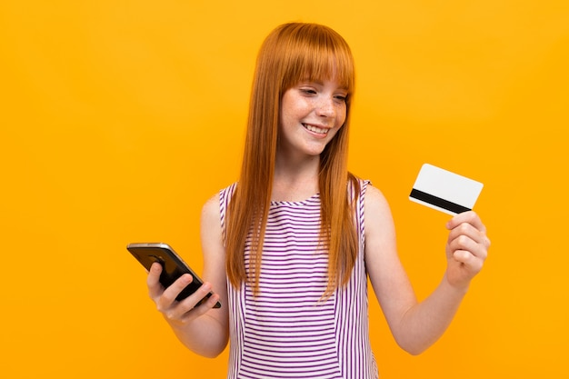 Zufrieden gestelltes rothaariges europäisches mädchen, das eine kreditkarte und ein telefon in ihren händen lokalisiert hält