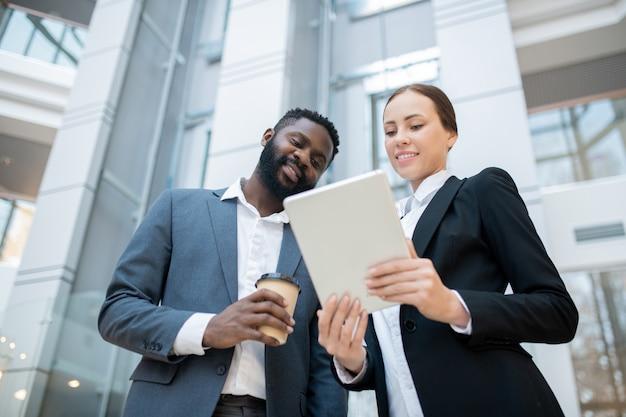 Zufrieden junge multiethnische kollegen in anzügen, die im büro stehen und tablets verwenden, während sie über online-berichte diskutieren