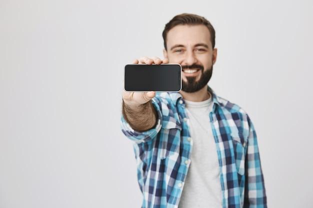 Zufrieden lächelnder bärtiger mann, der smartphonebildschirm, anwendungswerbung zeigt