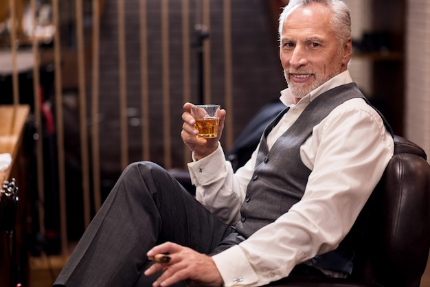 Zufrieden mit dem schnäppchen. hübscher gut gekleideter alter mann, der auf ledersessel mit cognacglas und zigarre sitzt.