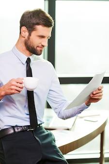 Zufrieden mit der geleisteten arbeit. hübscher junger mann in hemd und krawatte, der kaffeetasse hält und dokument untersucht, während er sich am schreibtisch lehnt