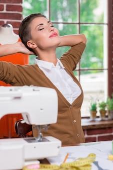 Zufrieden mit der geleisteten arbeit. zufriedene junge modedesignerin, die hände hinter dem kopf hält und die augen geschlossen hält, während sie an ihrem arbeitsplatz sitzt