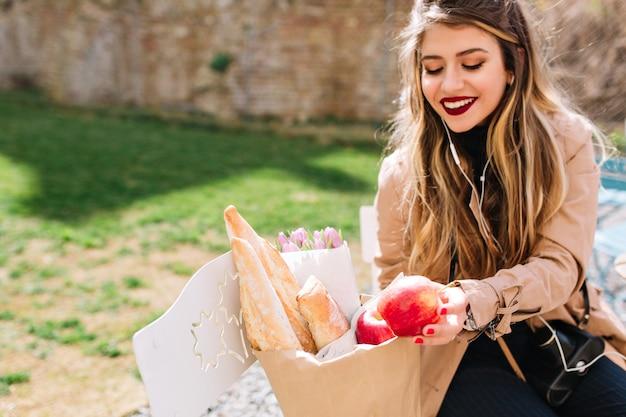 Zufrieden mit einkaufsmädchen mit großem lächeln beim betrachten ihrer einkäufe. attraktive junge frau, die lacht und essen in der papiertüte faltet, während sie im park sitzt.