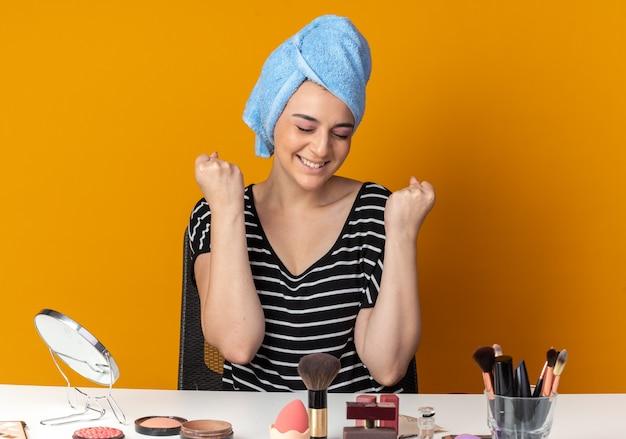 Zufrieden mit geschlossenen augen sitzt das junge schöne mädchen am tisch mit make-up-tools, die haare in ein handtuch gewickelt haben und die ja-geste einzeln auf der orangefarbenen wand zeigen