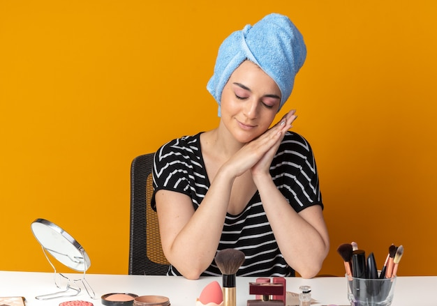 Zufrieden mit geschlossenen augen sitzt das junge schöne mädchen am tisch mit make-up-tools, die haare in ein handtuch gewickelt haben und die schlafgeste einzeln auf der orangefarbenen wand zeigen