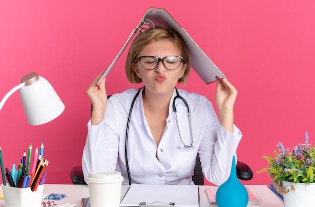 Zufrieden mit geschlossenen augen sitzt die junge ärztin, die ein medizinisches gewand mit stethoskop und brille trägt, am schreibtisch mit medizinischen werkzeugen bedeckten kopf mit ordner isoliert auf rosa wand