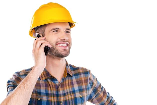 Zufrieden mit getaner arbeit. glücklicher junger männlicher tischler in bauarbeiterhelm, der am handy spricht und lächelt, während er vor weißem hintergrund steht