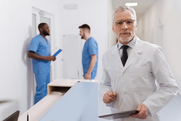 Zufrieden mit meiner verantwortung. alternder selbstbewusster weiser professor, der im krankenhaus arbeitet und in der nähe des krankenschwesterbüros steht, während er tablette hält