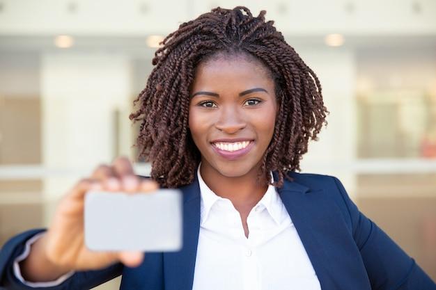 Zufriedene afroamerikanergeschäftsfrau, die leere karte hält