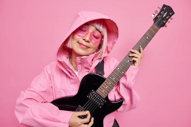 Zufriedene anführerin der jazzband spielt akustikgitarre neigt den kopf hält die augen vor vergnügen geschlossen genießt lieblingsmelodie trägt jacke kapuze auf dem kopf rosa farbtöne musik ist die nummer eins in meinem leben