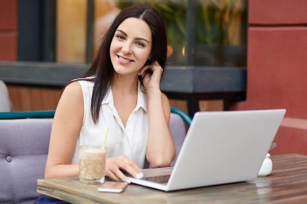 Zufriedene, angenehm aussehende freiberuflerin schaut distanziert mit notebook, trinkt milchshake, schaut positiv in die kamera, mag ihre arbeit, posiert im restaurant im freien, verbunden mit highspeed-internet