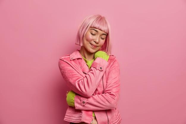 Zufriedene asain frau hat rosa haare umarmt sich schließt die augen in modischer jacke gekleidet.
