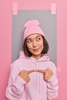 Zufriedene asiatin hat einen verträumten ausdruck und denkt an etwas gesten mit zeigefingern schaut weg, gekleidet in bequemen sweatshirt-posen gegen eine leere studiowand