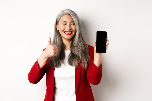 Zufriedene asiatische ältere geschäftsfrau, die leeren smartphonebildschirm und daumen hoch zeigt, online-werbung oder firmen-app lobend, über weißem hintergrund stehend.