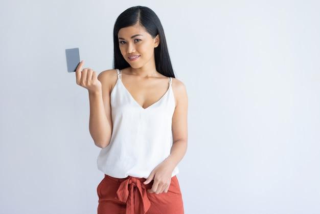 Zufriedene asiatische frau, die kreditkarte für die zahlung verwendet