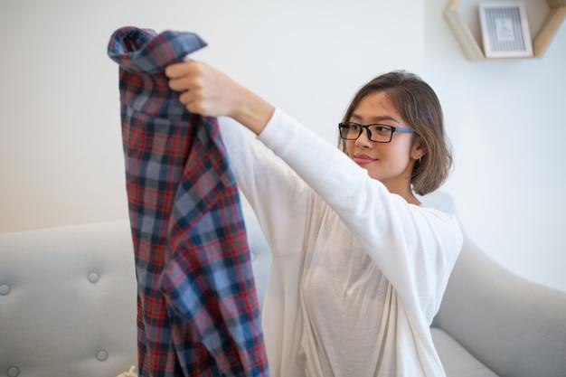 Zufriedene asiatische junge frau, die zu hause hemd anhebt