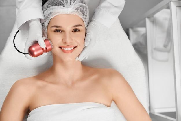 Zufriedene attraktive frau in kosmetikerin auf verfahren