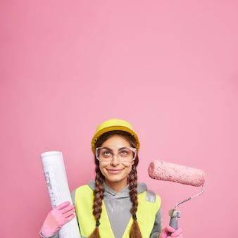 Zufriedene baumeisterin oder architektin hält den kopf sicher im helm trägt schutzbrille hält farbroller und blaupause liefert den besten service aller zeiten verwendet werkzeug für reparaturen, bereit für herausforderungen