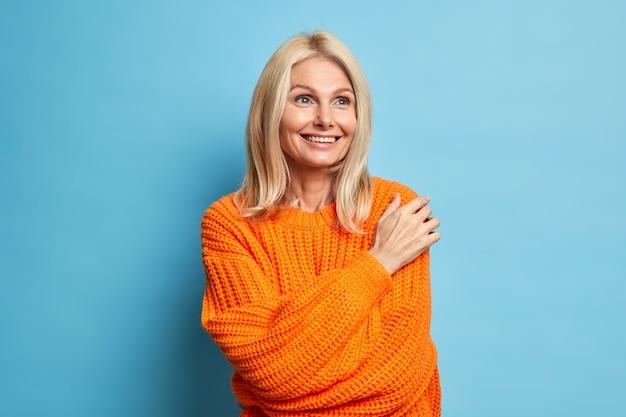 Zufriedene blonde frau mittleren alters hat einen verträumten ausdruck, lächelt sanft und denkt an etwas angenehmes, das einen bequemen strickpullover trägt.
