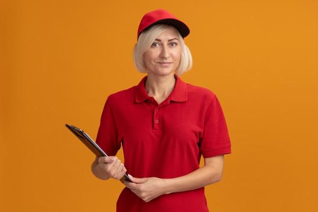 Zufriedene blonde lieferfrau mittleren alters in roter uniform und mütze mit klemmbrett
