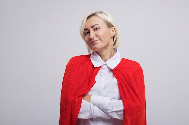 Zufriedene blonde superheldin mittleren alters im roten umhang