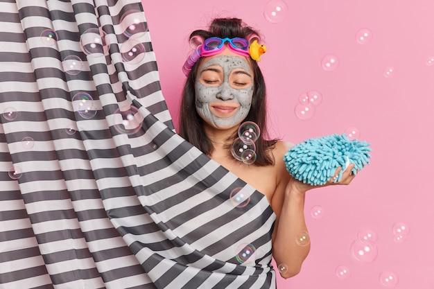 Zufriedene brünette frau hält die augen geschlossen hält badeschwamm nimmt dusche versteckt nackten körper hinter vorhang macht lockige frisur kümmert sich um haut wird hygienischen verfahren unterzogen. duschkonzept